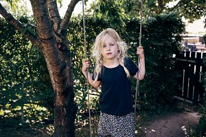 Cute little girl playing on a tree s