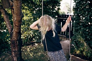 Shy little girl playing on a tree sw