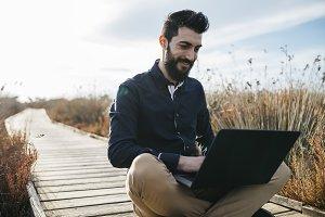 Content man enjoying laptop in natur
