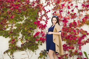 young pregnant lady posing against wall with creeping ivy