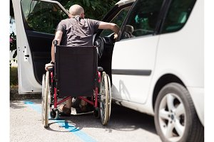Adult Driver In Wheelchair Getting Into The Car