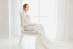Bride in wedding sitting on chair.