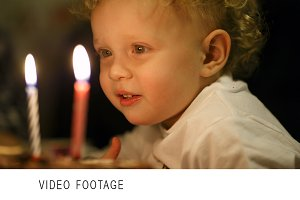 Little boy blowing out two candles