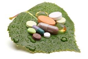 vitamins, tablets and pills on leaf