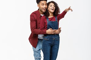 full length of smiling African American boyfriend and girlfriend pointing away isolated on white background.