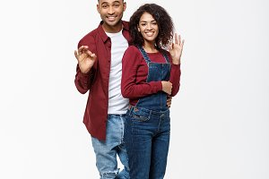 Lifestyle Concept - Full length portrait of a happy smiling african couple standing and showing ok gesture isolated over white background