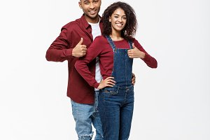 Lovely African American couple gesturing thumbs up to camera.