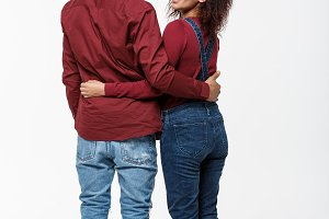 Full lenght back view of young African American couple hugging together isolated on white background