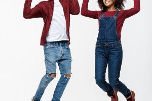 Lifestyle ,happiness and people concept: Happy young lovely African American couple jumping over bright grey background.