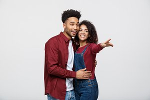Young African American people in casual clothes looking away and point finger. isolated on white background