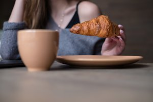 Woman holding delicious croissant