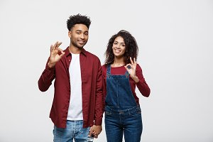 Portrait of a cheerful young african couple standing together and showing ok gesture isolated over white background