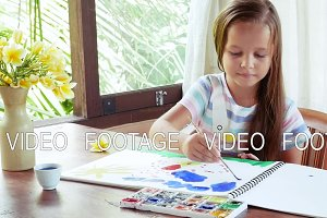 Child artist painting watercolor paints