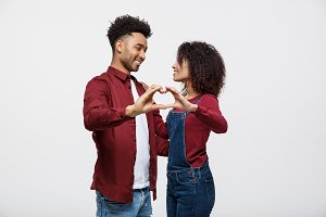 Portrait of a smiling young african couple dressed in casual clothes hugging and showing heart gesture with fingers isolated over white background