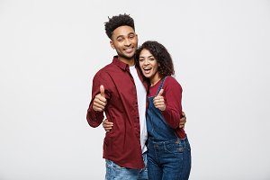 Portrait of attractive African american couple showing thumb up over white studio background.