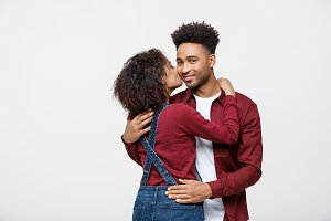 Close-up of African American young couple kissing over white background studio