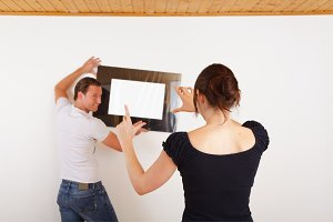 Young Couple Setting Up A Picture Frame
