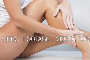 Woman with perfect body applying refreshing cream or body lotion on her legs, Concept depilation, skincare, cosmetics