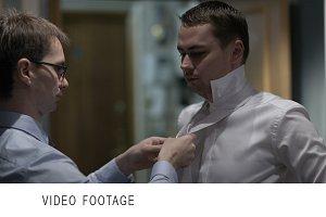 Groomsman tying groom's tie.