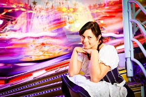 Young Woman Sitting Next To Carousel
