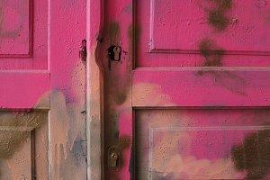 Locked wooden old door, pink, ruined