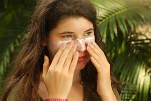 teenager girl using sun protecion cream on face close up photo