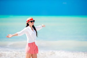 Young beautiful woman on white sand tropical beach. Caucasian girl with hat background the sea