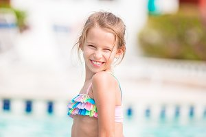 Adorable little girl relax near swimming pool