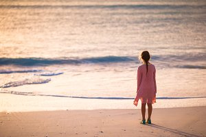 Adorable happy little girl walking on white beach at sunset.