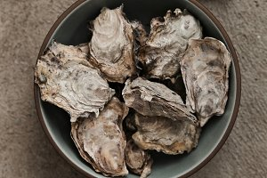 Bowl of fresh oysters with shucker