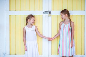 Adorable little girls on summer vacation background traditional caribbean house