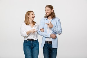 Portrait young happy couple love smiling embracing point finger to empty copy space, man and woman smile looking up, isolated over white background