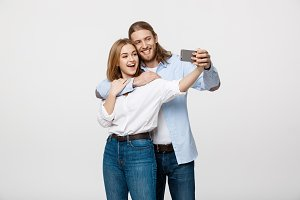 Portrait of a happy couple making selfie photo with smartphone over isolated white studio background.