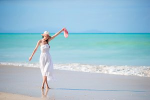 Young beautiful woman on white sand tropical beach. Caucasian girl with hat in white dress background the sea