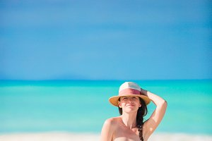 Young beautiful woman on white sand tropical beach. Caucasian girl with hat in dress background the sea