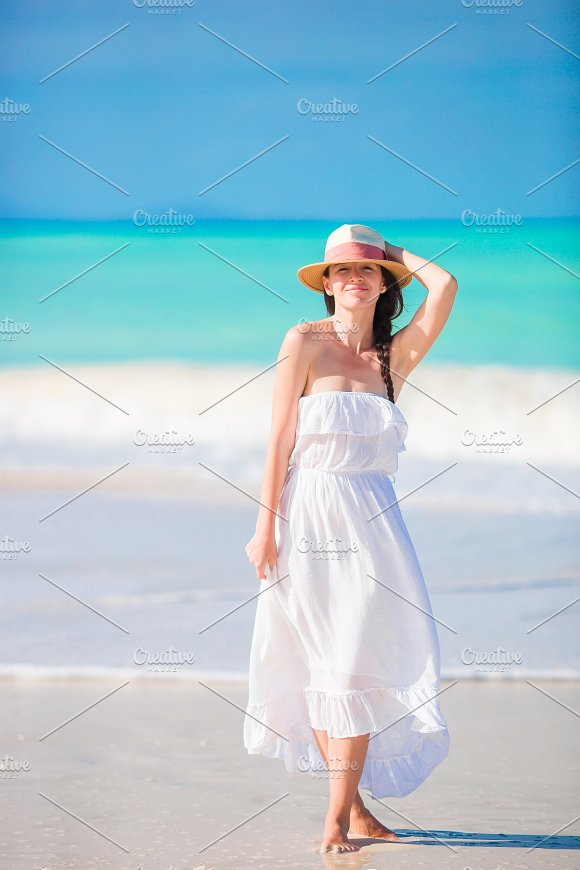 Young Beautiful Woman On White Sand Tropical Beach Caucasian With Hat In Dress Background