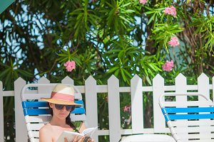 Young woman reading book near swimming pool
