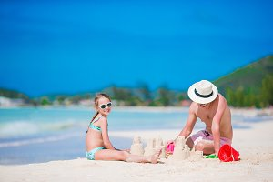 Family making sand castle at tropical white beach. Father and girl playing with sand on tropical beach