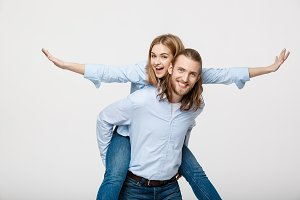 Portrait of smiling man giving happy woman a piggyback ride.