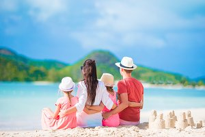 Family of four making sand castle at tropical white beach