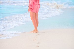Human footprints on the white sandy beach with beautiful young woman background