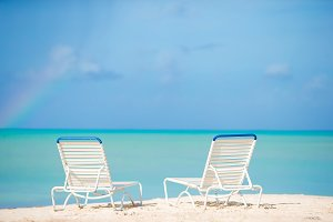White lounge chairs on a beautiful tropical beach at Maldives