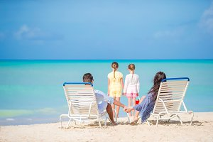 Happy beautiful family of four on the beach. Parents relaxing on sunbed and kids having fun on the coast