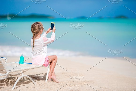 Little Girl Making Video Or Photo With By Her Camera Sitting On The Sunbed