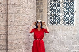 woman in red dress with hat and sunglasses standing