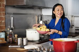 Asian woman cooking pasta