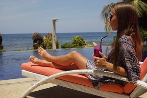 Girl with a glass of cocktail near to the pool.