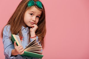 Thoughtful girl with a book on pink