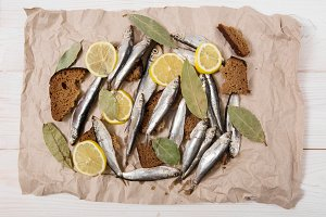 Sprat,bread,lemon,spice.Flat lay.