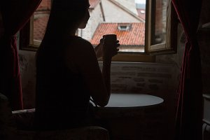 silhouette of a girl drinking tea at the table at the window in the room